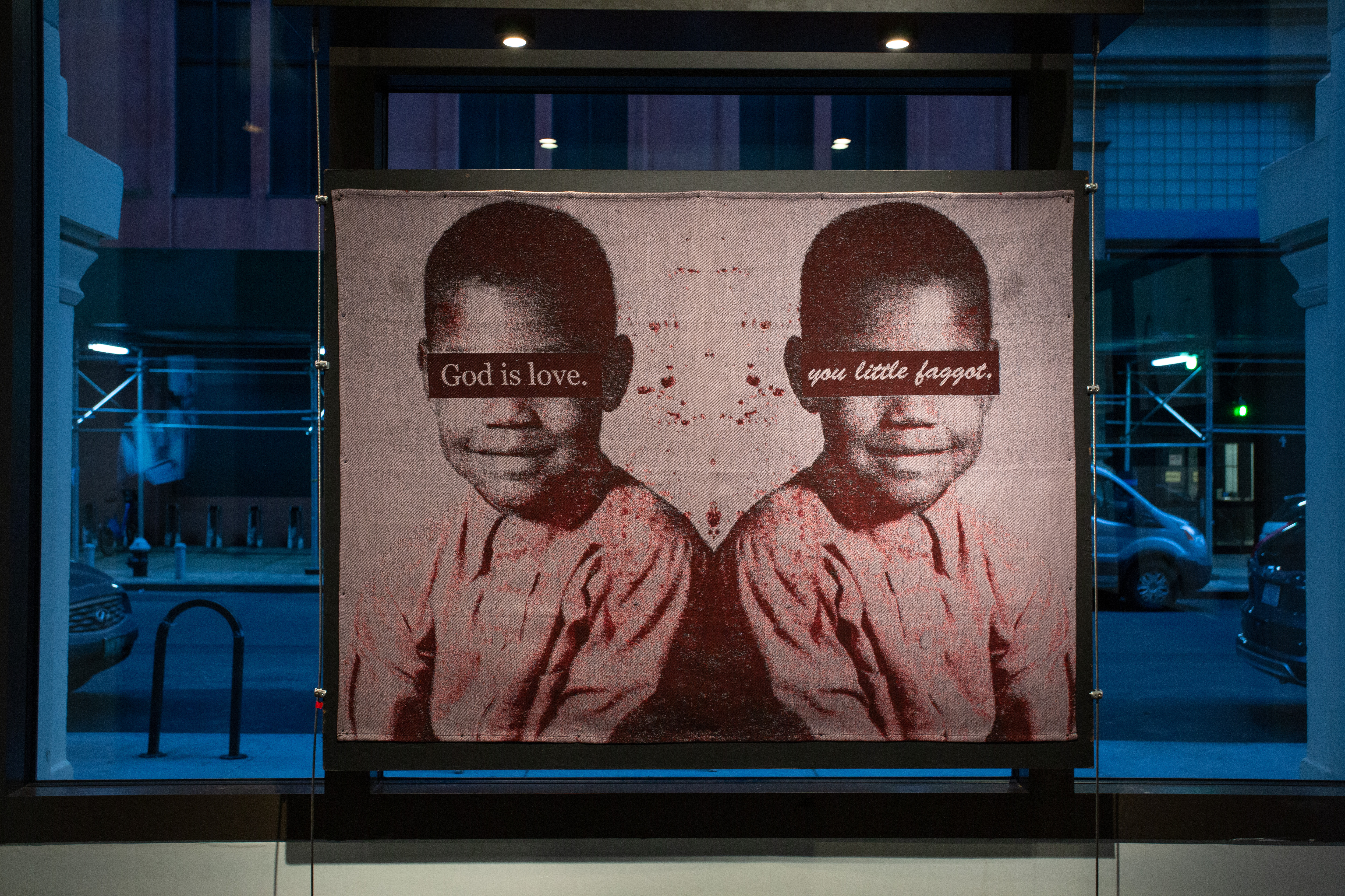 """Tapestry with a mirrored image of a young black boy. Over both sets of eyes, a black bar reads """"God is love. You little faggot."""""""