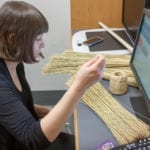 A woman sits in front of a computer monitor, sewing together straw to create a broom.