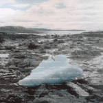 A single chunk of ice sits atop a barren rocky landscape. Small white text is arranged horizontally across the entire image.