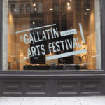 "An exterior shot of a building, showing the window of a gallery with vinyl lettering spelling out ""Gallatin Arts Festival""."