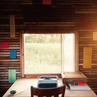 La fotogrqafía muestra la instalación The Hut, de Julie Ann. Interior de una cabaña con escritorio, silla, máquina de escribir y poemas clavados a las paredes de madera