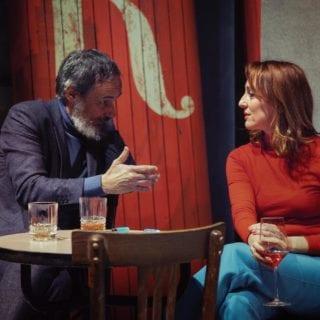 Hombre y mujer dialogando en la mesa de un bar