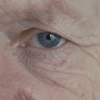 Primer plano del ojo izquierdo azul de un anciano