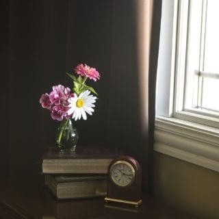 Esquina de habitación. Mesa con flores frescas junto a un reloj