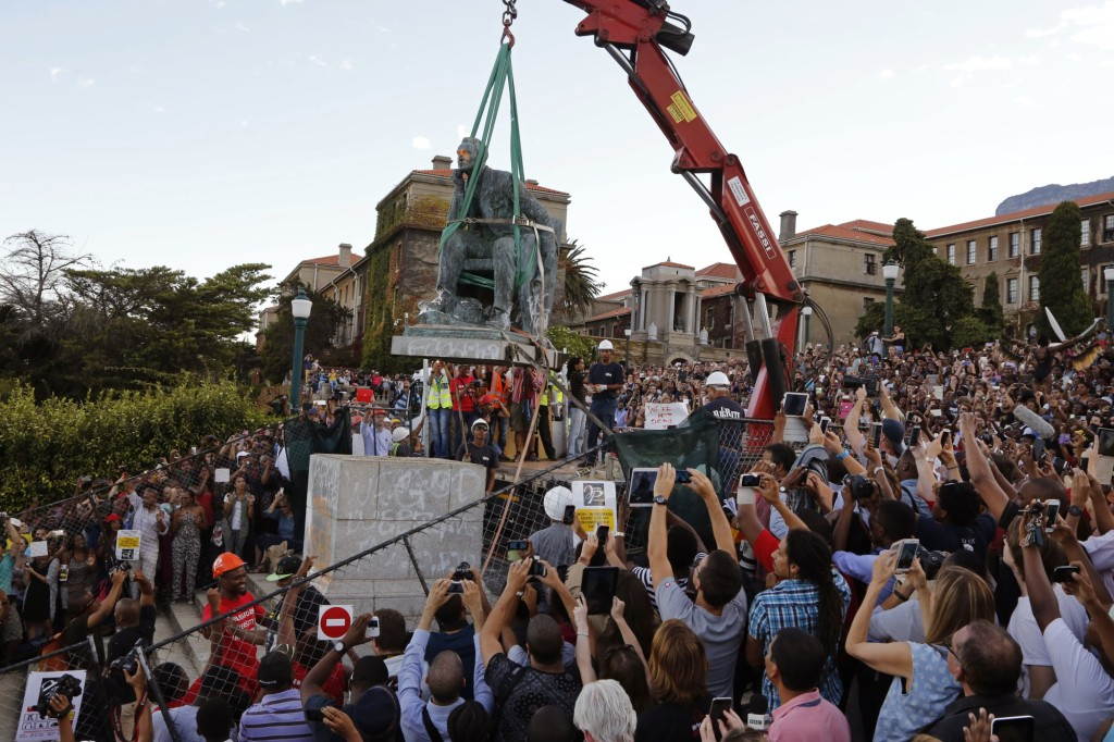 Cheering students surround the decades old bronze statue of British colonialist Cecil John Rhodes, as it is removed from the campus at the Cape Town University, Cape Town, South Africa, Thursday, April 9, 2015, responding to student protests describing it as symbolic of slow racial change on campus. Cecil Rhodes lived from 1853 until 1902, he was a businessman and politician in South Africa and was a fervent believer in British colonial rule. (AP Photo/Schalk van Zuydam)