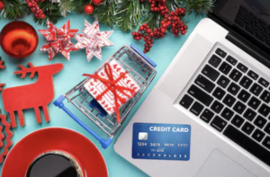 holiday themed image showing open laptop with credit card near track-pad, coffee and holiday themed items are visible near the laptop