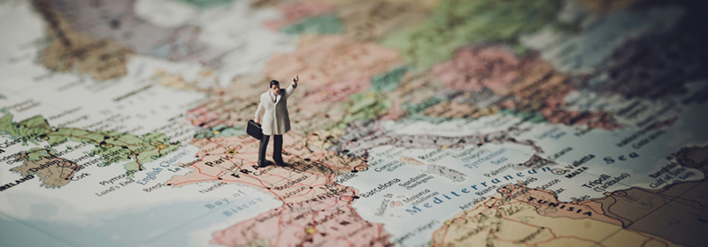 Miniture figurine standing on a map of Europe holding a suitcase with an air raised as if hailing a cab.