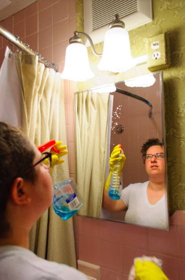 person cleaning bathroom mirror
