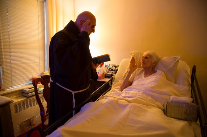 priest praying with bedridden figure