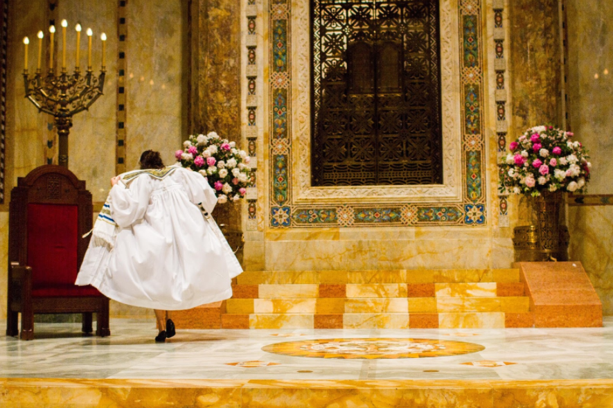 figure in flowing white outfit on an altar