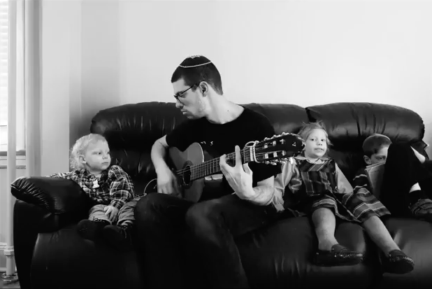 man in yarmulke playing guitar to two children