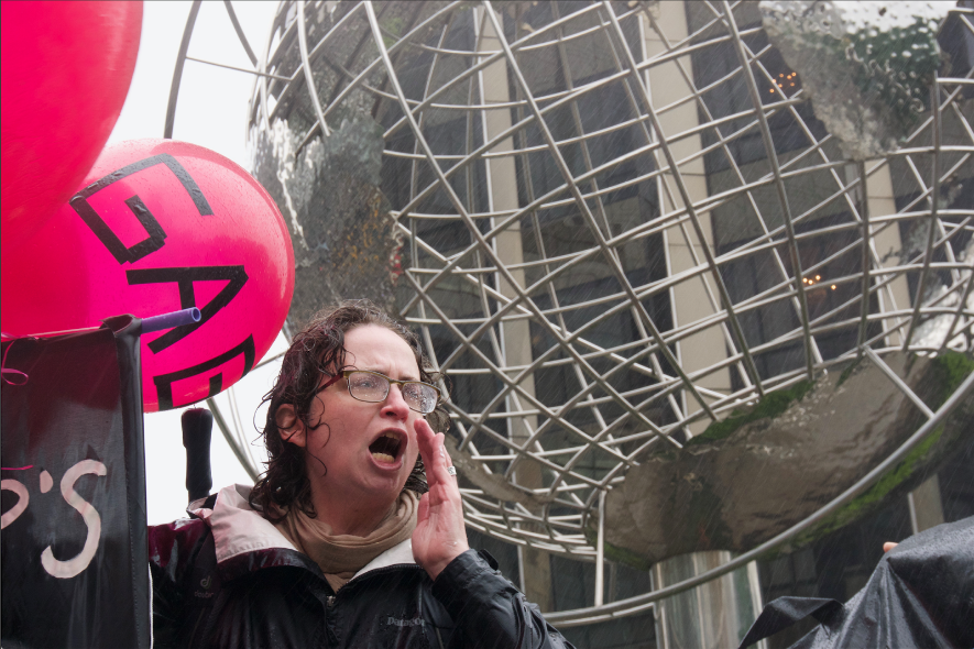 person screaming in front of metal globe sculpture