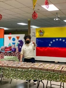 Niurka stands in room with Venezuelan flag