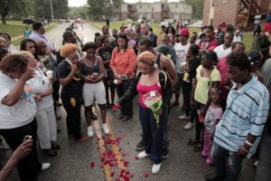 Lesley McSpadden dropping rose petals on the blood stains from her 18-year-old son Michael Brown, who was shot and killed by police in Ferguson, Mo. on Saturday, Aug. 9, 2014. (Photo: AP Photo/St. Louis Post-Dispatch, Huy Mach) http://www.dailymail.co.uk/wires/ap/article-2721021/Missouri-crowd-shooting-Kill-police.html