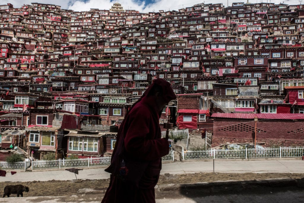 A Buddhist nun with a prayer wheel in Larung Gar, a monastic camp where thousands of nuns and monks live and study, in Sichuan Province, China. Credit Gilles Sabrié for The New York Times