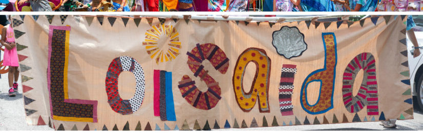 """This image is a textile handcrafted banner that says """"Loisaida"""" with each letter made of a differently patterned fabric."""