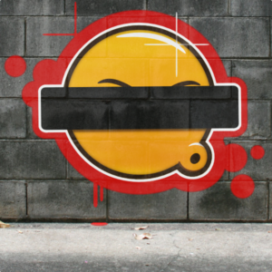Graffiti of yellow whistling cartoon face with eyes barred out